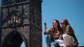 Dos mujeres que sientan y que toman un selfie en un fondo de la torre del puente de Charles Bridge en Praga metrajes
