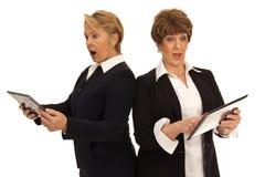 Dos mujeres que sostienen las tabletas y que parecen chocadas Foto de archivo libre de regalías