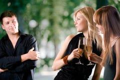 Dos mujeres que sostienen los vidrios con champán y que ríen, hombre joven Foto de archivo