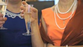 Dos mujeres que sostienen los vidrios con el vino espumoso almacen de metraje de vídeo