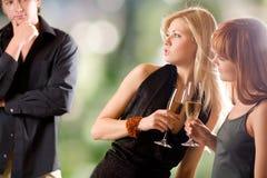 Dos mujeres que sostienen los vidrios con la mirada del champán y del hombre joven Fotografía de archivo libre de regalías