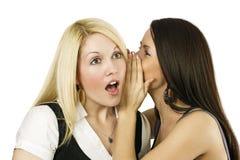 Dos mujeres que susurran secretos Foto de archivo libre de regalías