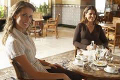 Dos mujeres que tienen bebidas en restaurante Imágenes de archivo libres de regalías