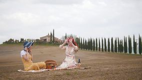 Dos mujeres que tienen una comida campestre, comiendo las frutas y hablando - Toscana, el camino de los árboles de ciprés almacen de metraje de vídeo