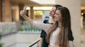 Dos mujeres que toman un selfie mientras que hace compras almacen de metraje de vídeo