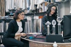 Dos mujeres que trabajan con las telas para las cortinas, tapicería, hembras eligen telas usando el ordenador Diseñador del lugar imágenes de archivo libres de regalías