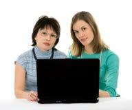 Dos mujeres que trabajan en una computadora portátil. Aislado en blanco Fotos de archivo libres de regalías