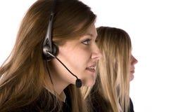 Dos mujeres que trabajan uno con el receptor de cabeza Imágenes de archivo libres de regalías