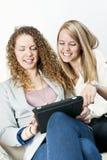 Dos mujeres que usan el ordenador de la tablilla Foto de archivo libre de regalías