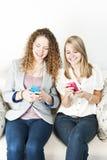 Dos mujeres que usan los dispositivos móviles Imágenes de archivo libres de regalías