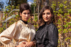 Dos mujeres ropa victoriana, eje y reloj de sol en th Imagen de archivo