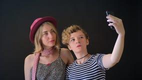 Dos mujeres rubias bastante jovenes que abrazan y que toman el selfie, aislado en fondo negro del estudio almacen de video
