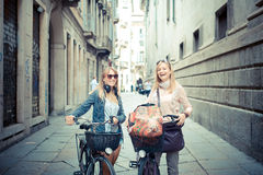 Dos mujeres rubias hermosas que hacen compras en la bici Foto de archivo