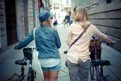 Dos mujeres rubias hermosas que hacen compras en la bici Fotos de archivo libres de regalías