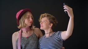 Dos mujeres rubias jovenes encantadoras que abrazan y que toman el selfie, colocándose aislado en fondo negro almacen de metraje de vídeo