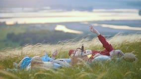 Dos mujeres rubias que mienten en el campo y que miran el cielo mientras que teniendo una comida campestre almacen de metraje de vídeo