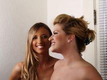 Dos mujeres rubias sonrientes descubren a amigos de los hombros Fotografía de archivo libre de regalías