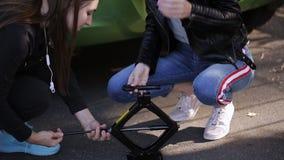 Dos mujeres saben actuar Jack para cambiar una rueda pinchada del coche almacen de video