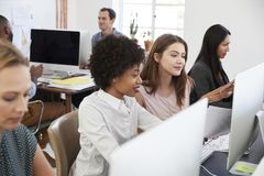Dos mujeres se sentaron en un ordenador discuten el trabajo en oficina abierta del plan fotos de archivo