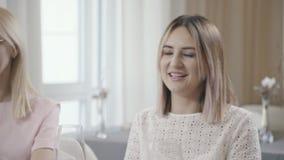 Dos mujeres similares comunican con los amigos en un café y una sonrisa almacen de video