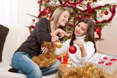 Dos mujeres sonrientes con la decoración de la Navidad Imágenes de archivo libres de regalías