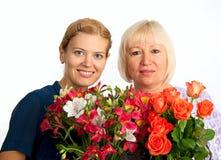 Dos mujeres sonrientes con las flores en el fondo blanco Foto de archivo