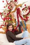 Dos mujeres sonrientes con los encadenamientos de la Navidad Imágenes de archivo libres de regalías
