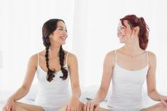 Dos mujeres sonrientes en los top sin mangass blancos que se sientan en cama imagenes de archivo