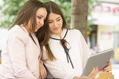 Dos mujeres sonrientes jovenes hermosas que se sientan en un banco y una mirada Fotografía de archivo