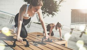 Dos mujeres sonrientes jovenes, muchachas en la ropa de deportes que hace ejercicios mientras que escucha la música Entrenamiento imagen de archivo