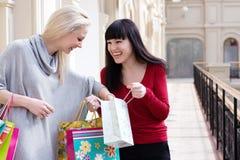 Dos mujeres sonrientes que hacen compras con los bolsos coloreados Fotografía de archivo