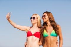 Dos mujeres sonrientes que hacen el selfie en la playa Foto de archivo libre de regalías