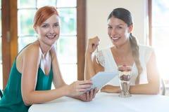 Dos mujeres sonrientes que se sientan en restaurante con una tableta digital Imagen de archivo libre de regalías