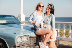 Dos mujeres sonrientes que se unen cerca del coche del vintage Fotos de archivo libres de regalías