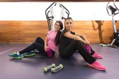Dos mujeres sonrientes que sientan la relajación en el gimnasio, sentándose en piso Foto de archivo