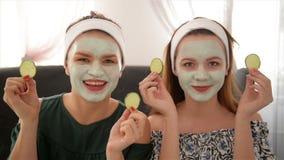 Dos mujeres sonrientes que sostienen los pepinos Retrato de muchachas en salón del balneario Concepto de la belleza de la salud,  almacen de video