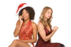 Dos mujeres una de la Navidad que hablan en el teléfono celular Imagen de archivo libre de regalías