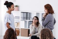 Dos mujeres valientes que colocan y que miran uno a durante el papel que paga en la reunión de la ayuda de la psicoterapia foto de archivo libre de regalías