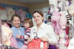 Dos mujeres y niño en la tienda de la ropa Imágenes de archivo libres de regalías