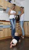 Dos mujeres y un bebé en la cocina Fotografía de archivo libre de regalías