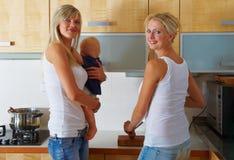 Dos mujeres y un bebé en la cocina Imágenes de archivo libres de regalías