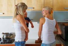 Dos mujeres y un bebé en la cocina Imagen de archivo libre de regalías