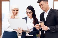 Dos mujeres y un hombre están bebiendo el café y están mirando algo en la pantalla del ordenador portátil imagen de archivo libre de regalías