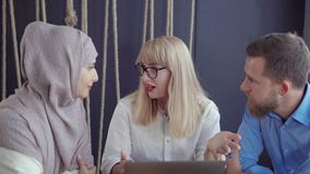 Dos mujeres y un hombre están discutiendo en el sitio, mirando en la pantalla del ordenador portátil almacen de video