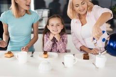 Dos mujeres y una muchacha que consigue lista para beber té con una empanada hecha en casa en su cocina Fotografía de archivo libre de regalías