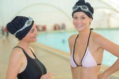 Dos nadadores que se preparan para competir con en el poo de la natación imagen de archivo libre de regalías