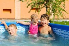 Dos hermanos y hermana del bebé en la piscina Imagenes de archivo