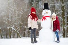 Dos niñas adorables que construyen un muñeco de nieve junto en parque hermoso del invierno Hermanas lindas que juegan en una niev Fotos de archivo libres de regalías