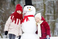 Dos niñas adorables que construyen un muñeco de nieve junto en parque hermoso del invierno Hermanas lindas que juegan en una niev Fotografía de archivo libre de regalías