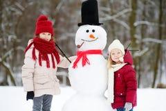Dos niñas adorables que construyen un muñeco de nieve junto en parque hermoso del invierno Hermanas lindas que juegan en una niev Imágenes de archivo libres de regalías